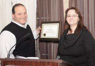 Councilman Joe Baldacci receives a Distinguished Citizen Award from the Maine Association of Interdependent Neighborhoods (MAIN) from Kandie Davenport-Desell at the spaghetti dinner that raised close to $5 thousand for a bus route. Photo by Ramona du Houx