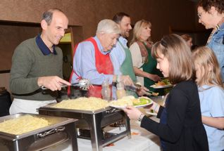 Governor John Baldacci serves Mika Boggins spaghetti. Over 400 people came to the Baldacci brother's fundraiser to save a bus route in Bangor.